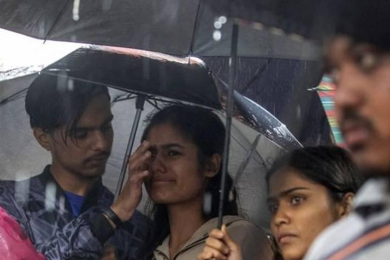 Mulher em prantos debaixo de um guara-chuva