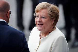 German Chancellor Angela Merkel arrives to attend the traditional Bastille Day military parade on the Champs-Elysees Avenue in Paris