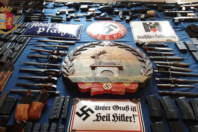 Foto divulgada pela polícia italiana mostra memorabília nazista e parte das várias armas apreendidas na operação desta segunda-feira (15)