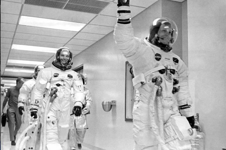 Antes de embarcarem na Apolo 11, Neil Armstrong (à dir.), Mike Collins e Buzz Aldrin (atrás) caminham rumo à espaçonave que os levaria à LuaNasa