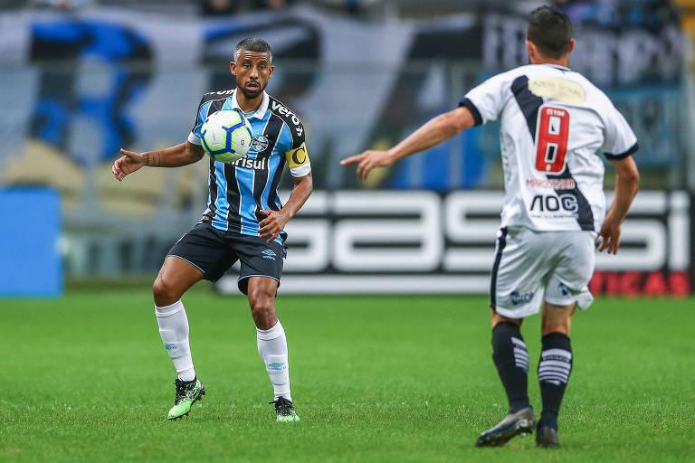 O lateral Leonardo Moura, do Grêmio, tenta passar pelo atacante vascaíno Marquinho, no duelo do Brasileirão na Arena do Grêmio