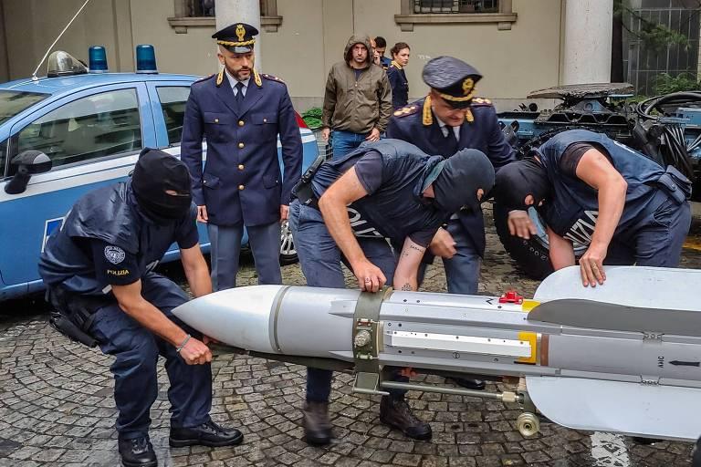 Policiais manejam míssil ar-ar, usado para derrubar aviões, apreendido em operação contra neonazistas em Turim