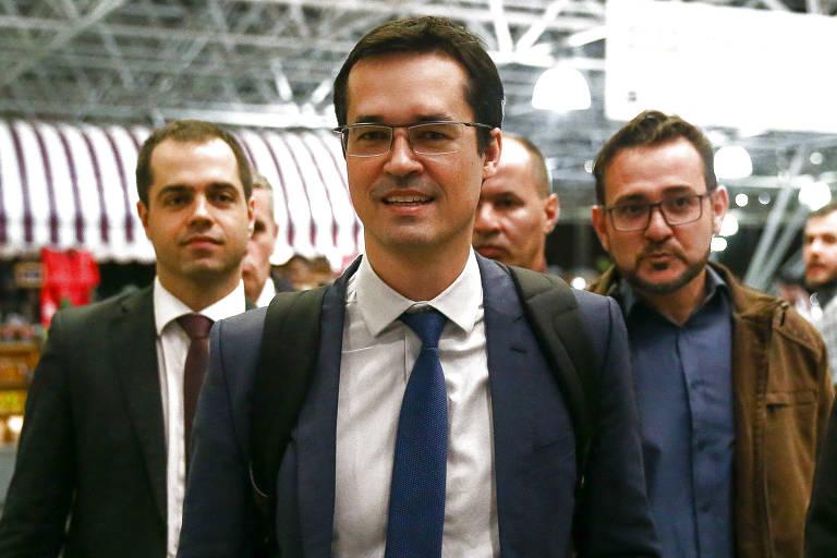 Deltan, de terno, sorri para a câmera no aeroporto; atrás dele há outros dois homens