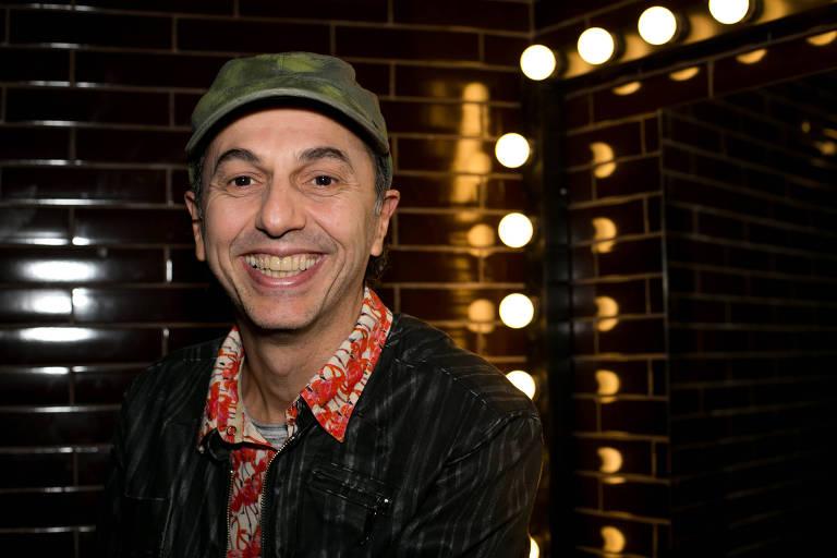 De boné verde, jaqueta preta e camisa social com detalhes em vermelho e branco, cantor Zeca Baleiro abre sorriso enquanto posa para foto