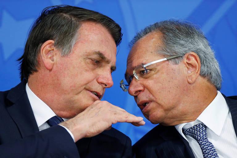 Na foto, o presidente Jair Bolsonaro conversa bom o ministro da Economia, Paulo Guedes. Ambos estão sentados, lado a lado, e inclinados um para o outro.  Gudes fala algo no ouvido de Bolsonaro, enquanto este faz um gesto com a mão direita