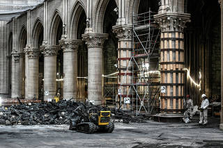 Workers stand next to an excavator robot during preliminary work in the Notre-Dame Cathedral, three months after a major fire, in Paris