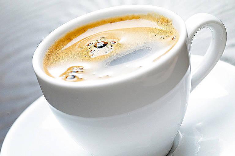 Na foto, uma xícara branca com café sob um pires branco