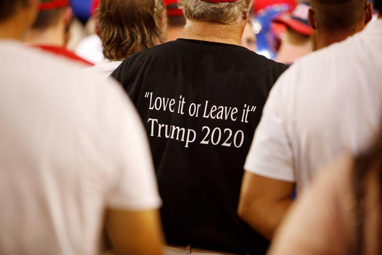 """Apoiador de Trump usa camisa com os dizeres """"Ame-os [os Estados Unidos] ou deixe-os"""" em comício na cidade de Greenville, na Carolina do Norte"""