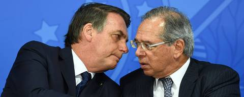 Brazilian President Jair Bolsonaro (L) and his Finance Minister Paulo Guedes talk during the inauguration ceremony of Gustavo Montezano as the new president of the National Bank for Economic and Social Development (BNDES) in Brasilia on July 16, 2019. (Photo by EVARISTO SA / AFP) ORG XMIT: ESA659
