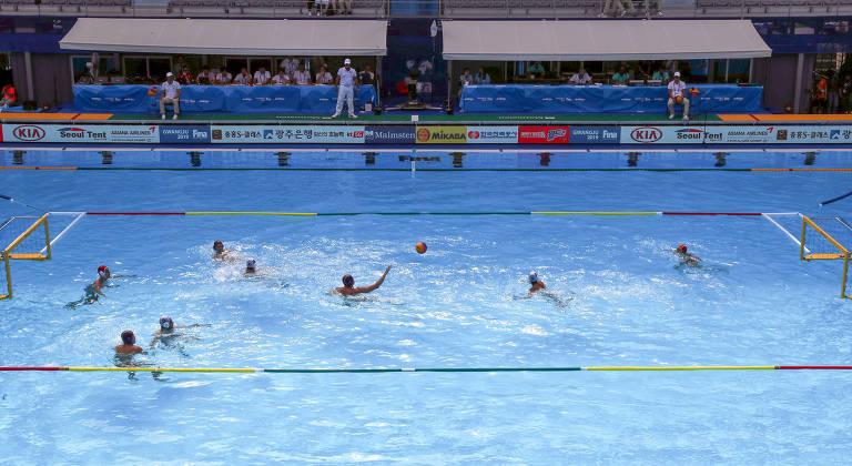 dentro da água, várias pessoas com os braços levantados