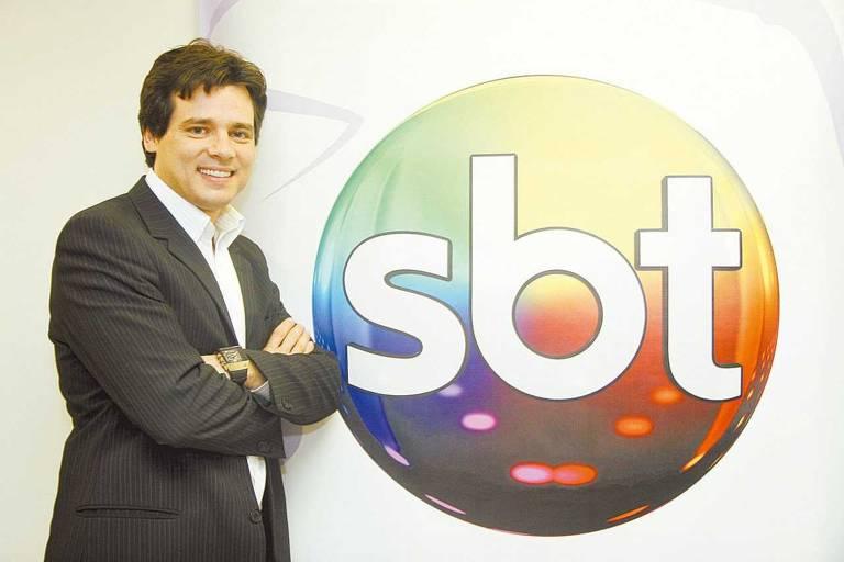 O apresentador Celso Portiolli posa ao lado do logo do SBT