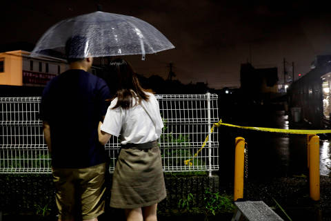 Shin Jun, a Chinese animation fan who lives in Osaka, and his girlfriend look at Kyoto Animation's studio building which was burnt out by arson attack after mourning for the victims in Kyoto, Japan, July 19, 2019. REUTERS/Kim Kyung-Hoon ORG XMIT: TOK753
