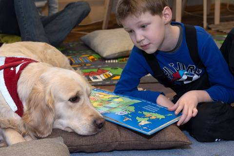 Kevin, 5, reads on February 26, 2014 to a dog hired by a library in Tartu, south Estonia to encourage kids to practice reading books aloud, to increase confidence of shy kids. A library in Estonia is getting children to read out loud to dogs to boost their literacy, self confidence and social skills with a little help from man's best friend. AFP PHOTO / Raigo Pajula /ESTONIA OUT ORG XMIT: 2008