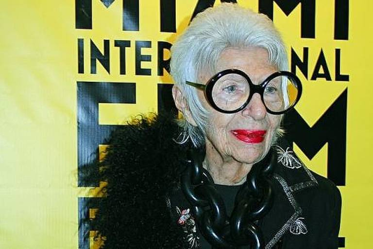 mulher branca idosa usa óculos com enormes aros pretos e veste roupa estilosa de couro preto e plumas
