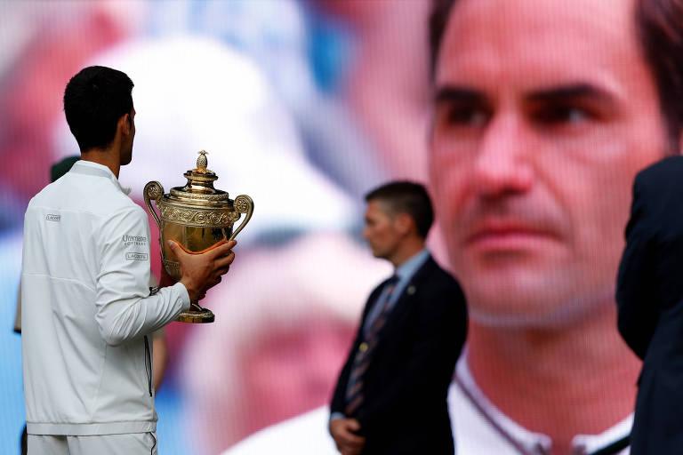 Djokovic com o trofeu de Wimbledon após vencer a final contra Roger Federer, que aparece no telão ao fundo