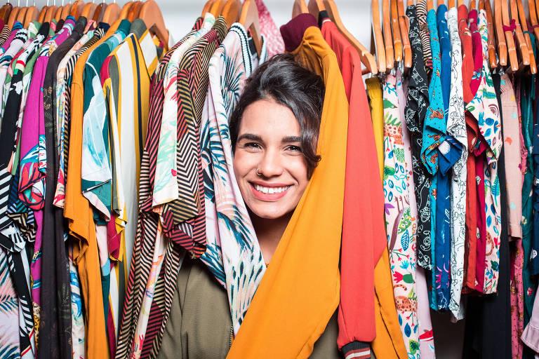 Cabeça de mulher sorrindo entre roupas em arara