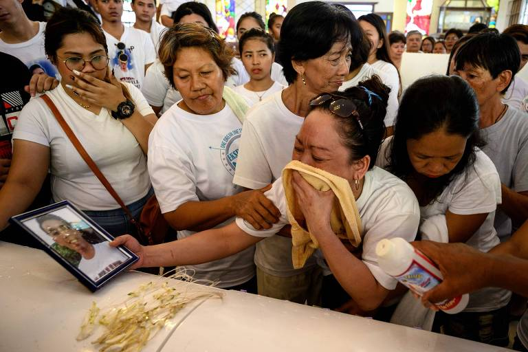 A filipina Maria Theresa Conje chora no enterro do filho Bryan, morto no contexto da guerra às drogas do país, em Manila