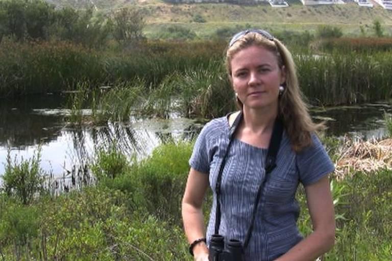 Em primeiro plano, mulher posa para foto. Segura binóculos. Ao fundo, vegetação rasteira e um córrego.