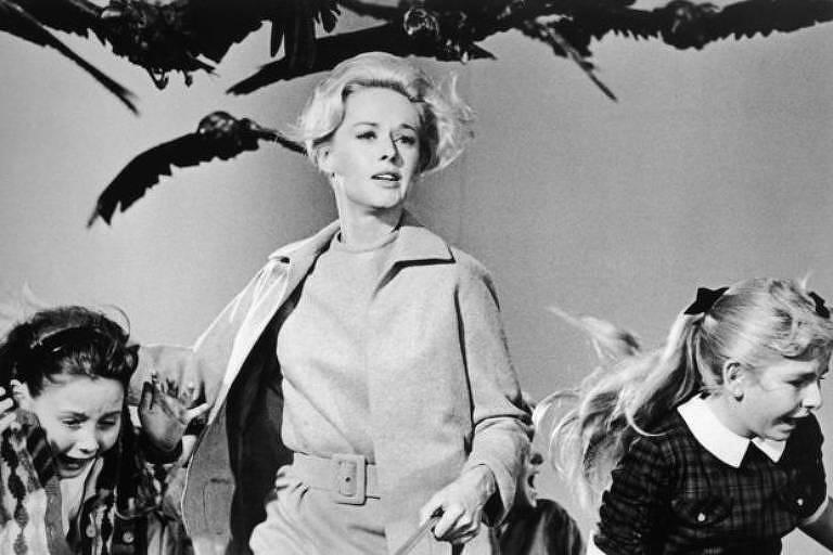 Mulher ao centro e duas crianças nas laterais são fotografadas em cena de filme. Exibem expressões de terror. Pássaros estão na parte superior da imagem.