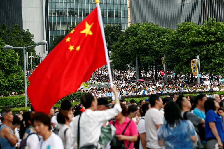 Manifestantes em ato de apoio ao governo de Hong Kong, pró-Pequim, carregam bandeiras chineses durante protesto