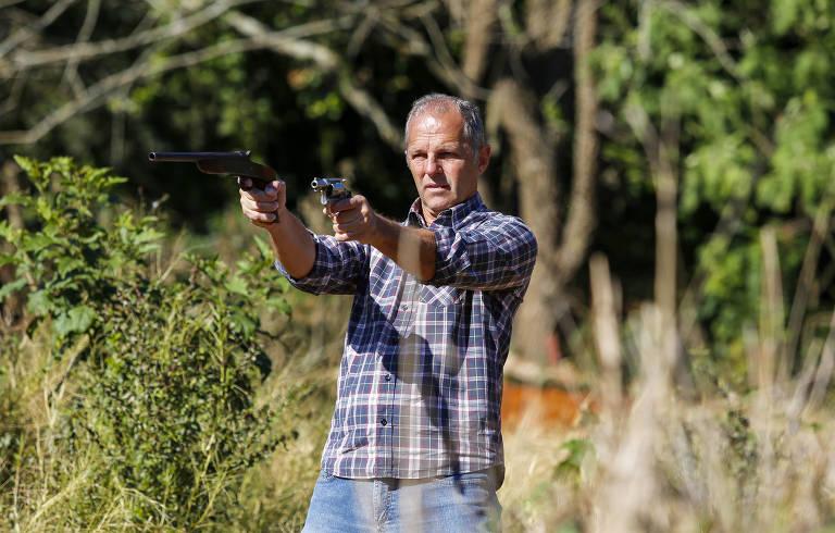 Djalma Pastorello mostra seu revólver 38 registrado e uma garrucha 32 sem registro em uma fazenda em Aparecidinha, em Foz do Iguaçu (PR)