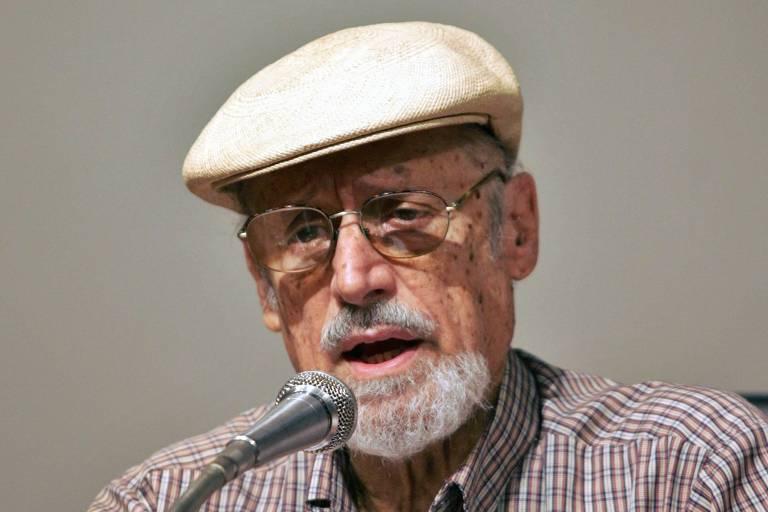 Homem idoso, de cavanhaque grisalho, utiliza boina branca e óculos, sentado atrás de uma mesa. Fotografado com expressão séria enquanto fala a um microfone posicionado à sua frente.