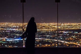 People look out over the Riyadh skyline at night from Al Faisaliyah tower, in Saudi Arabia. (Sergey Ponomarev/The New York Times)