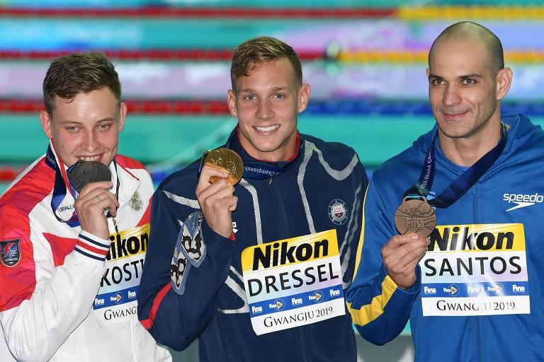 À direita, o brasileiro Nicholas Santos, que conquistou o bronze nos 50 m borboleta. A seu lado, o norte-americano Caeleb Dressel, que conquistou o ouro. À esquerda, Oleg Kostin, da Rússia, que ficou com a prata.