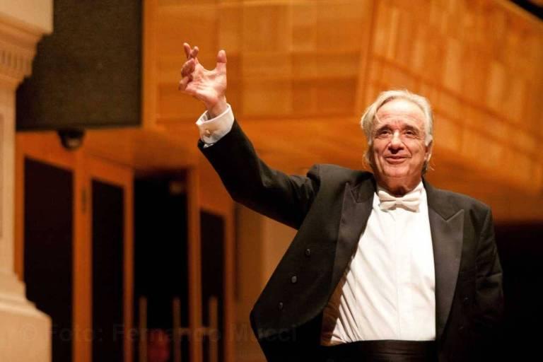 Maestro João Carlos Martins em concerto da Bachiana Filarmônica do Sesi-SP, na Sala São Paulo, em 2017. Na imagem, Martins está vestido de smoking e levanta o braço direito enquanto sorri