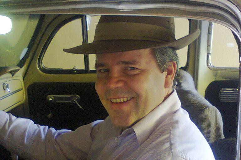 Homem de chapéu sorri ao volante de um fusca