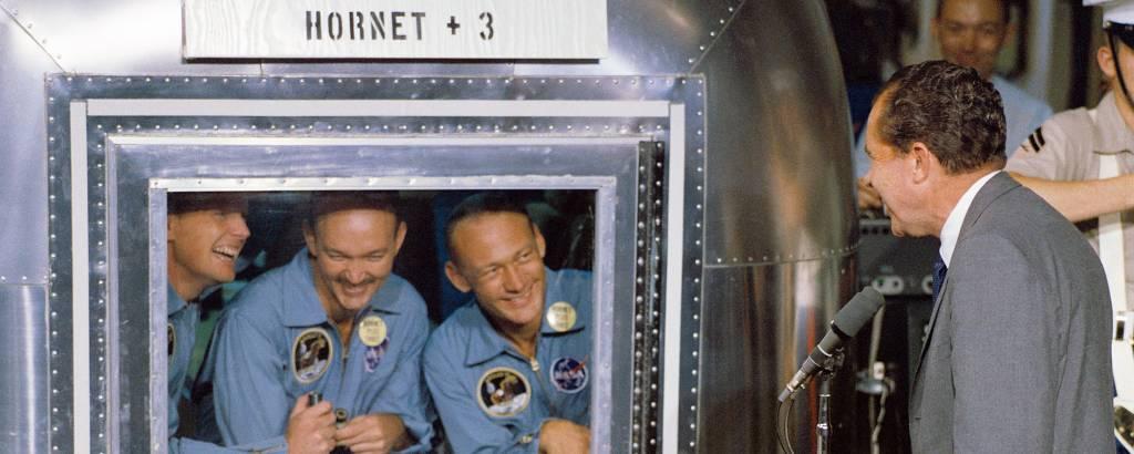 O então presidente americano Richard Nixon se encontra com Neil Armstrong, Michael Collins e Buzz Aldrin em unidade de quarentena