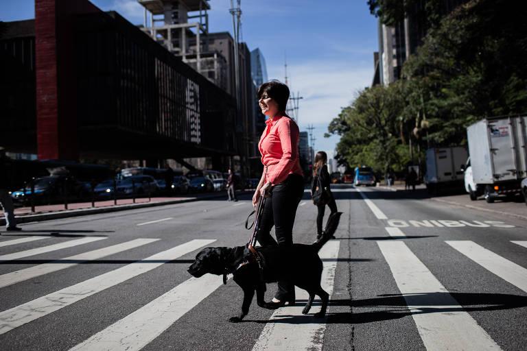 A advogada Thays Martinez, 45, pivô da lei que permitiu, há 20 anos, a presença de cão-guia em todos os estabelecimentos do país caminha com Sophie na avenida Paulista
