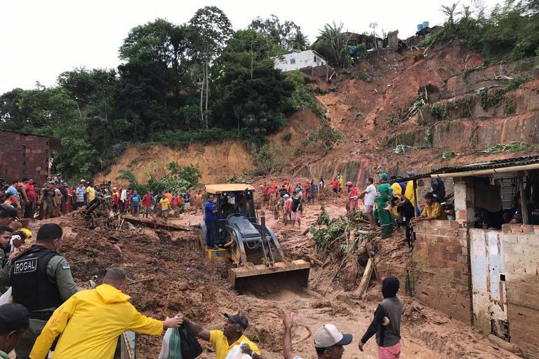 Moradores usam baldes para cavar lama e retirar corpo de grávida na Grande Recife