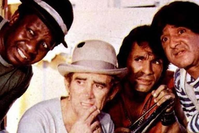 Da esquerda para a direita, Mussum, Didi, Dedé e Zacarias observam algo fora do quadro da foto, em cena do filme 'Os Saltimbancos Trapalhões', de 1981. Mussum está de chapéu preto, Didi, de chapéu banco, Dedé, de camisa vermelha, e Zacarias, de camiseta de manga longa, listrada em branco e azul, e um macacão branco por cima