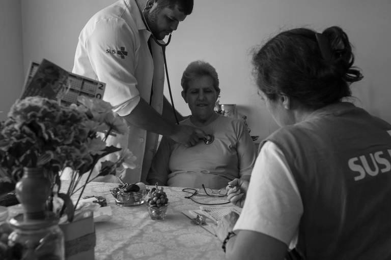 Médico Cássio Gonçalves atende a aposentada Isilda Florência Godinho, na zona sul de São Paulo, durante visita que faz parte do programa  Saúde da Família