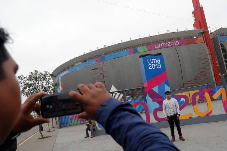 Homem posa para foto à frente do Estádio Nacial em Lima, no Peru