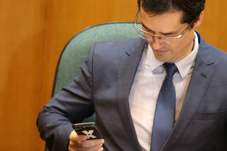 Brazil's prosecutor Deltan Dallagnol looks at his cellphone during a ceremony of the return of funds recovered by Operation Lava Jato to Petrobras, in Curitiba