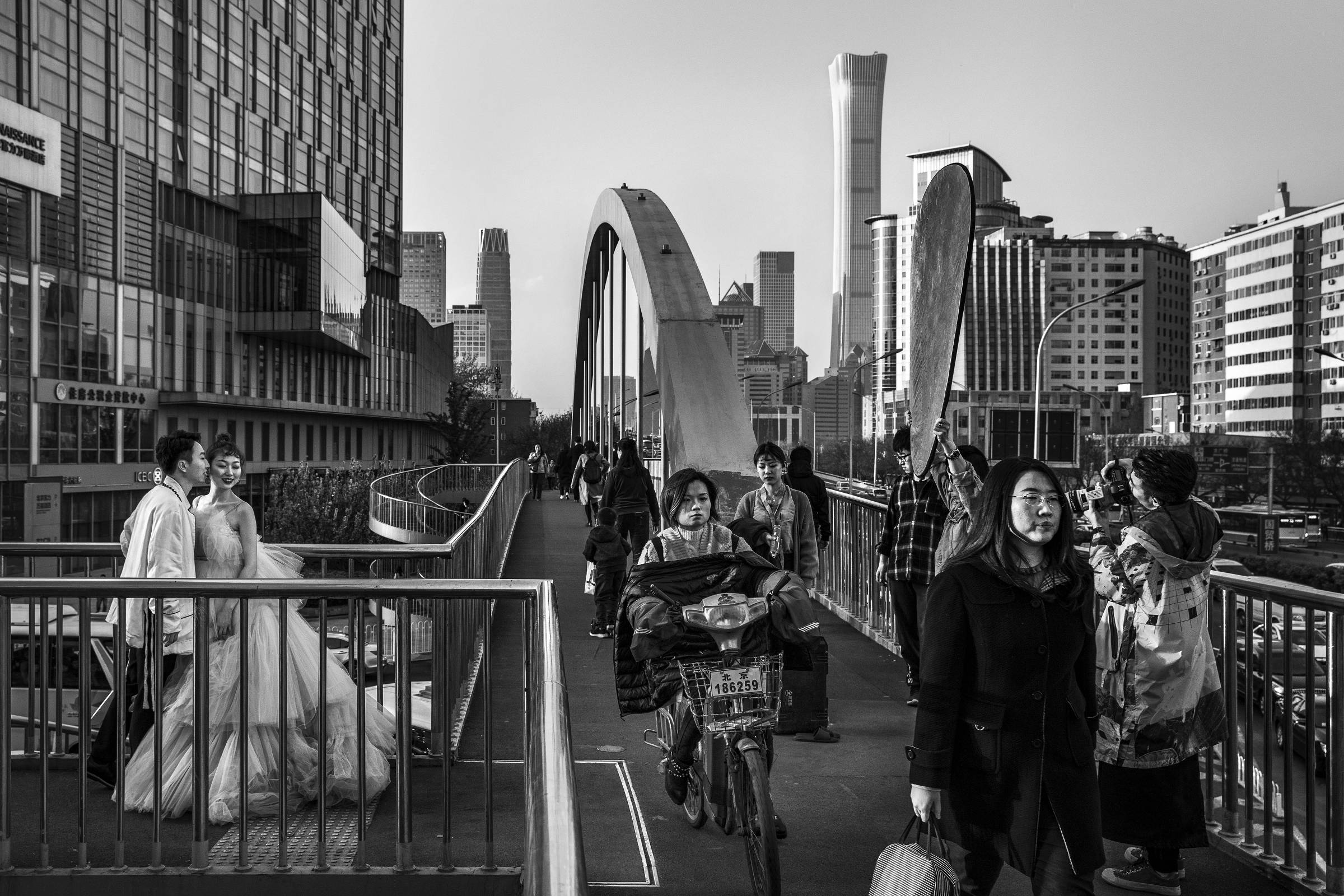 A newlywed couple poses for a photo on a Beijing viaduct