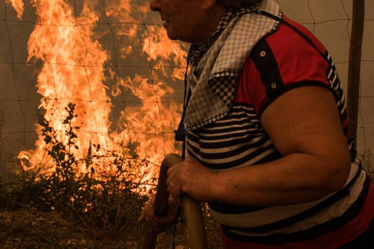 Mulher passa em frente a chamas