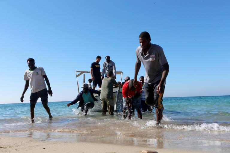 Migrantes chegam à praia após serem resgatados pela guarda costeira de Trípoli