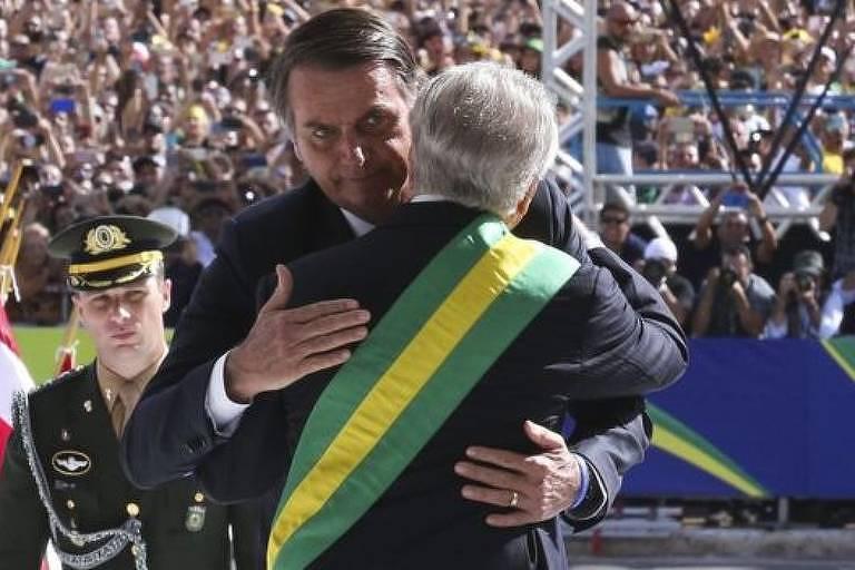 Em primeiro plano, Michel Temer, de costas e utilizando a faixa presidencial, cumprimenta o presidente Jair Bolsonaro durante cerimônia de posse. Em segundo plano, militar observa a cena. Ao fundo, multidão.