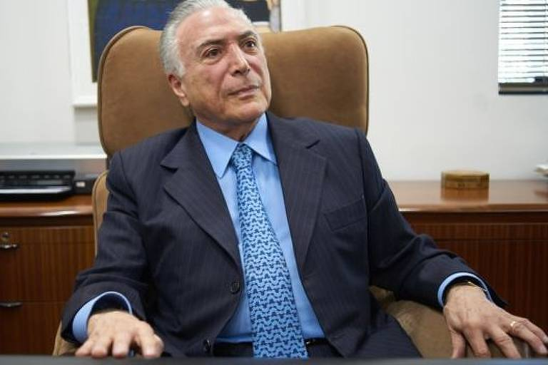 Ex-presidente Michel Temer, fotografado durante entrevista, usa terno preto e está sentado com os braços apoiados nos braços da poltrona.