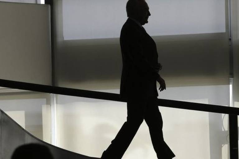 Silhueta do ex-presidente Michel Temer enquanto caminha em uma sala.