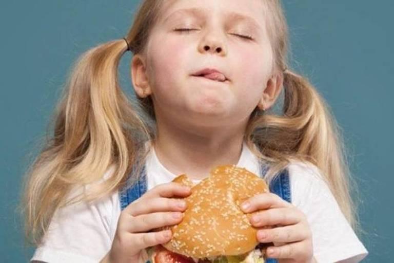 Garota jovem comendo um hamburguer