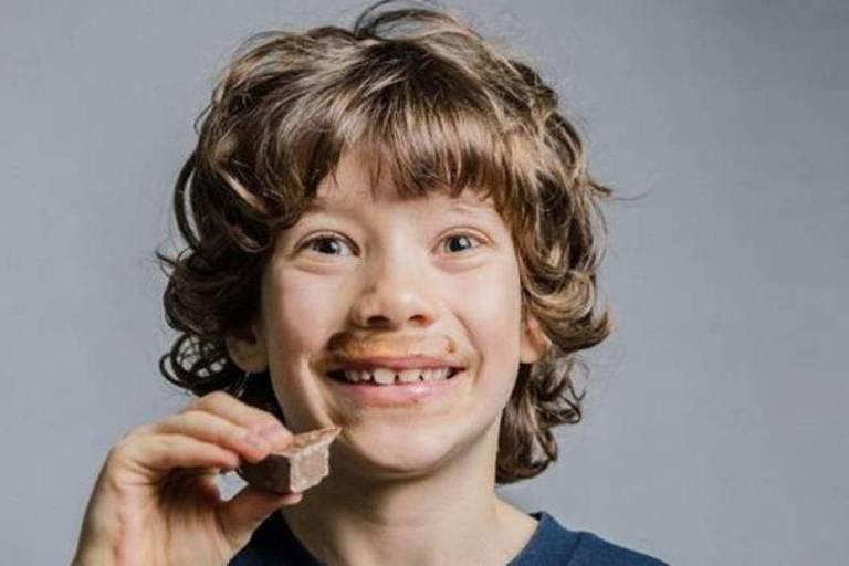 Garoto comendo pedaço de chocolate