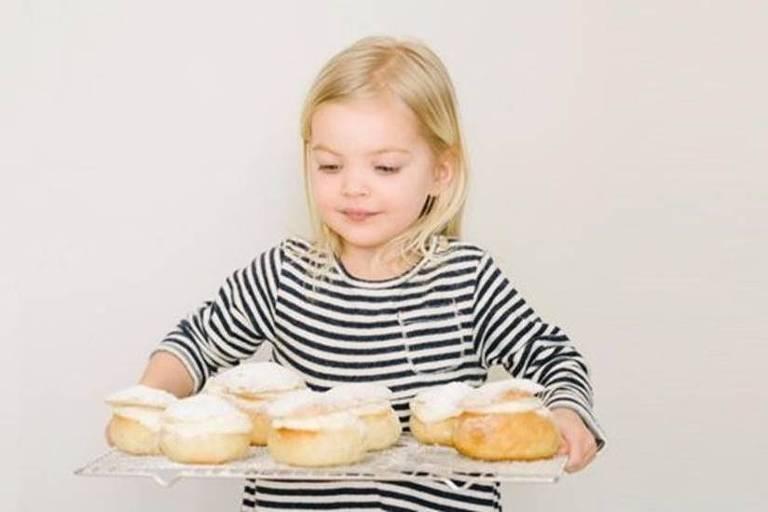 Garota segurando uma bandeja com doces