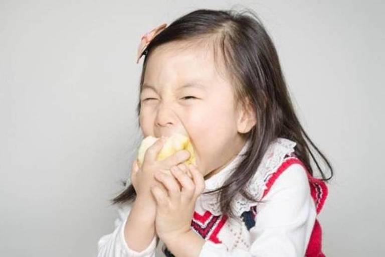 Garota asiática come uma maçã