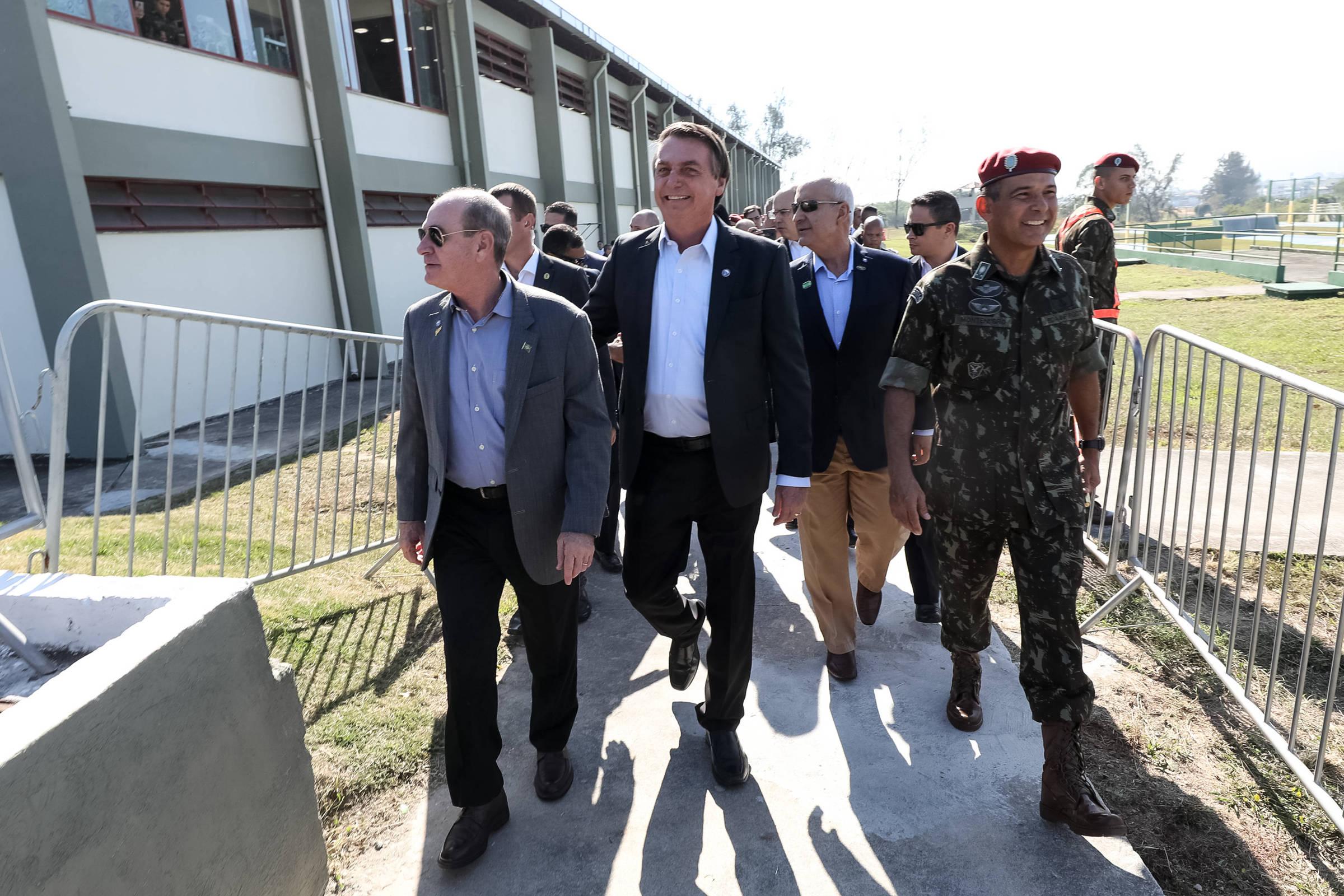 Presidente caminha acompanhado de outras pessoas durante cerimônia militar.