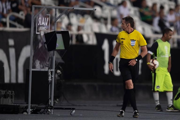 O árbitro Raphael Claus checa o VAR durante partida entre Botafogo e Atlético-MG, realizada no estádio Nílton Santos