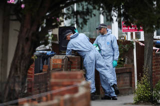 Forensic officers check for evidence in a bin on the street where a heavily pregnant woman was stabbed to death in the Thornton Heath area of London